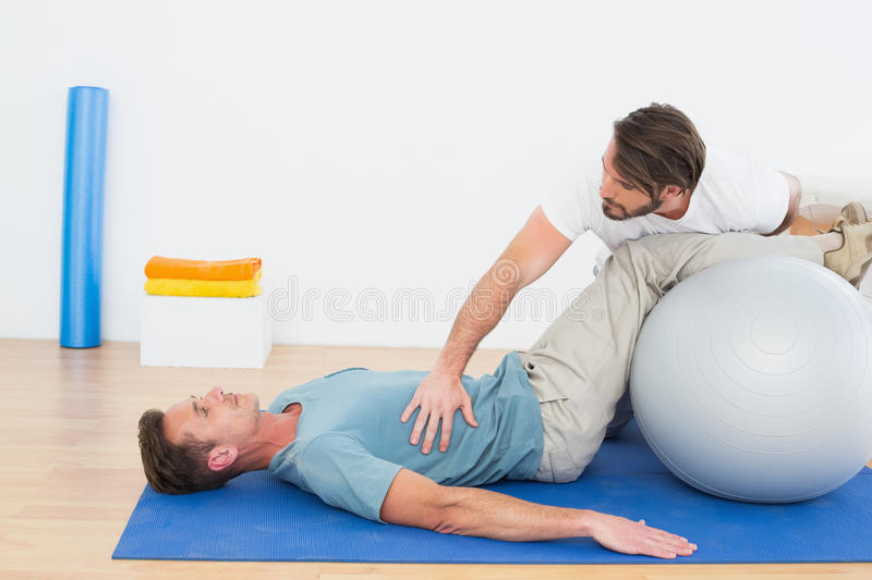 Physical therapist assisting young man with yoga ball stock photos