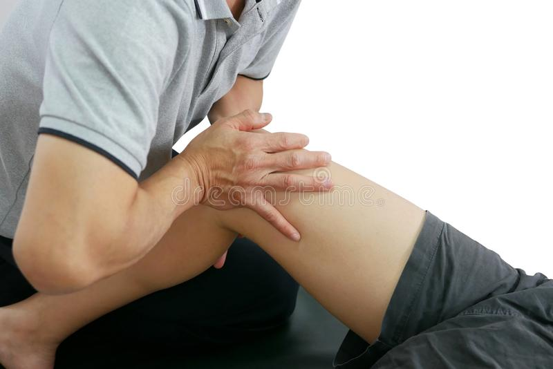 Physical therapist treats the knee to the patient on white background stock image