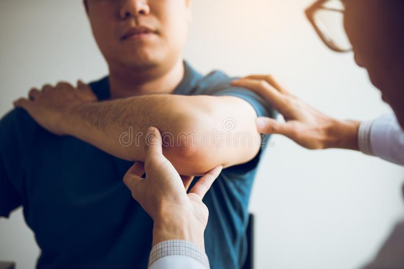 Physical therapists are checking patients elbows at the clinic office room.  royalty free stock photos