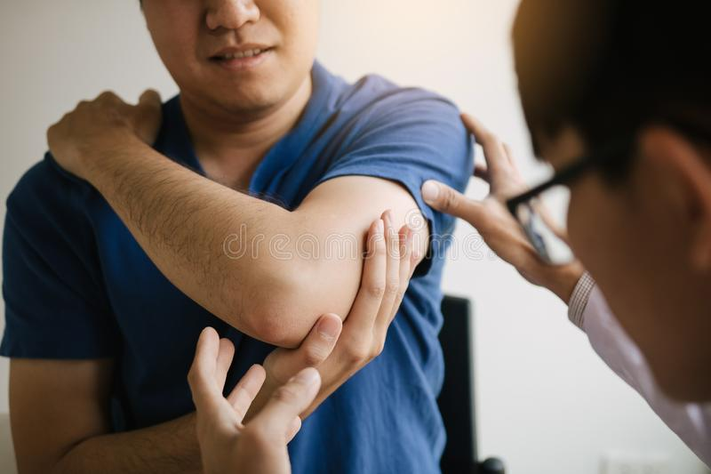 Physical therapists are checking patients elbows at the clinic office room.  royalty free stock image