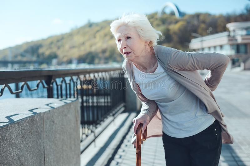 Physically exhausted woman doubling over with back pain. Intense pain. Tired elderly lady with a walking cane holding her hand on a lower back while feeling some royalty free stock photos