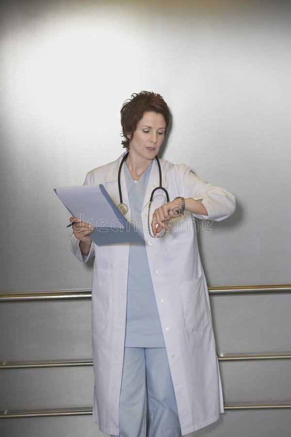 Download Physician Checking Wristwatch In Elevator Stock Photo - Image: 31839910