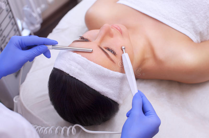The physician-cosmetologist makes Electric Facial Treatment of the skin of a beautiful, young woman in a beauty salon. royalty free stock photography