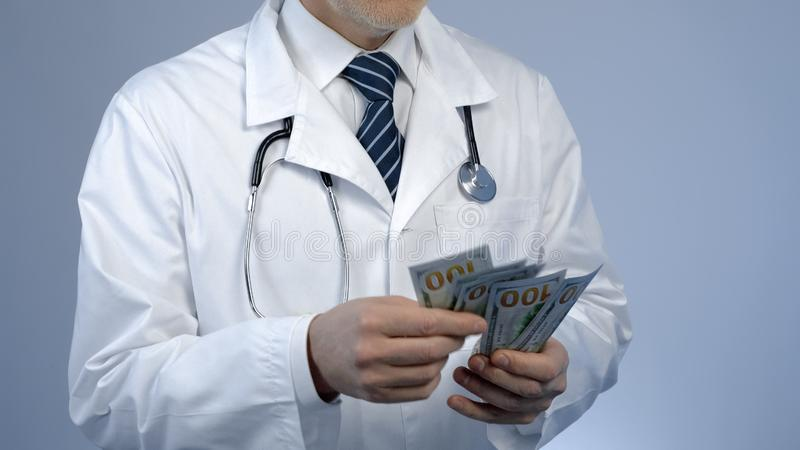 Physician counting bundle of money, expensive medicine at private clinic, bribe. Stock photo stock images