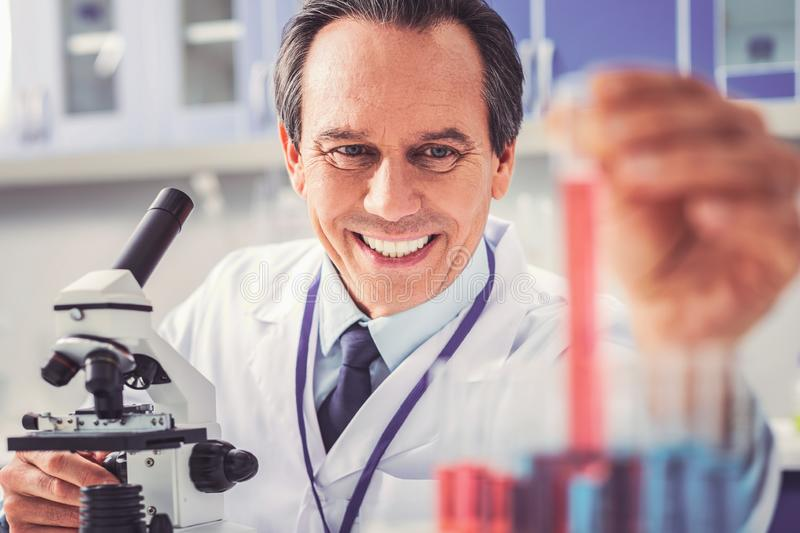 Physician feeling satisfied using new microscope. New microscope. Experienced skillful physician feeling very satisfied while using new modern microscope stock photo