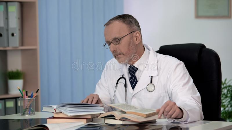 Physician reading medical books searching information about rare disease science royalty free stock photos