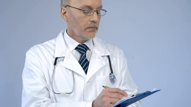 Physician with serious face writing in paper documents, keeping medical records royalty free stock photography