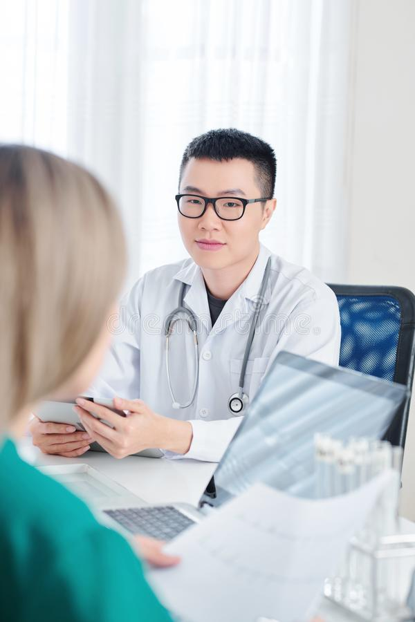 Physician talking to colleague royalty free stock image