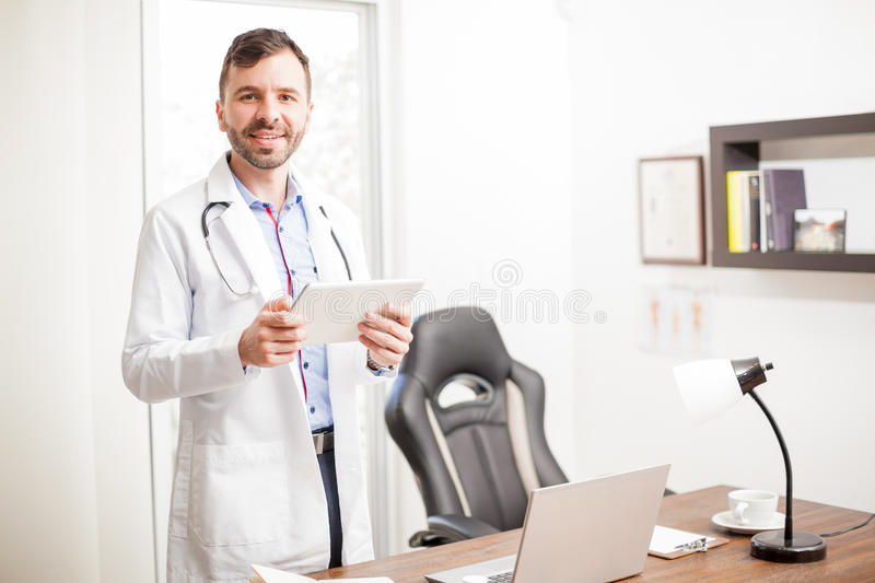 Physician using a tablet in his office royalty free stock images