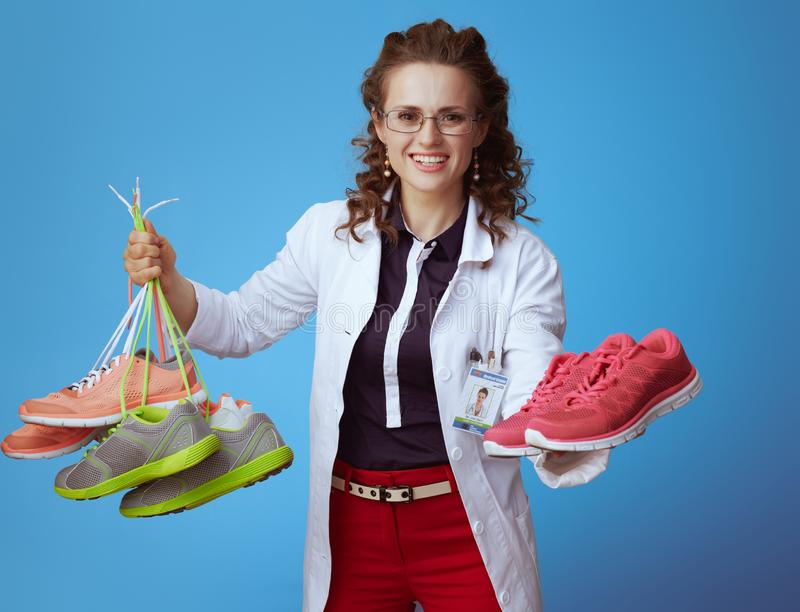 Physician woman giving one pair of fitness sneakers. Physician woman in bue shirt, red pants and white medical robe giving one pair of fitness sneakers while stock image