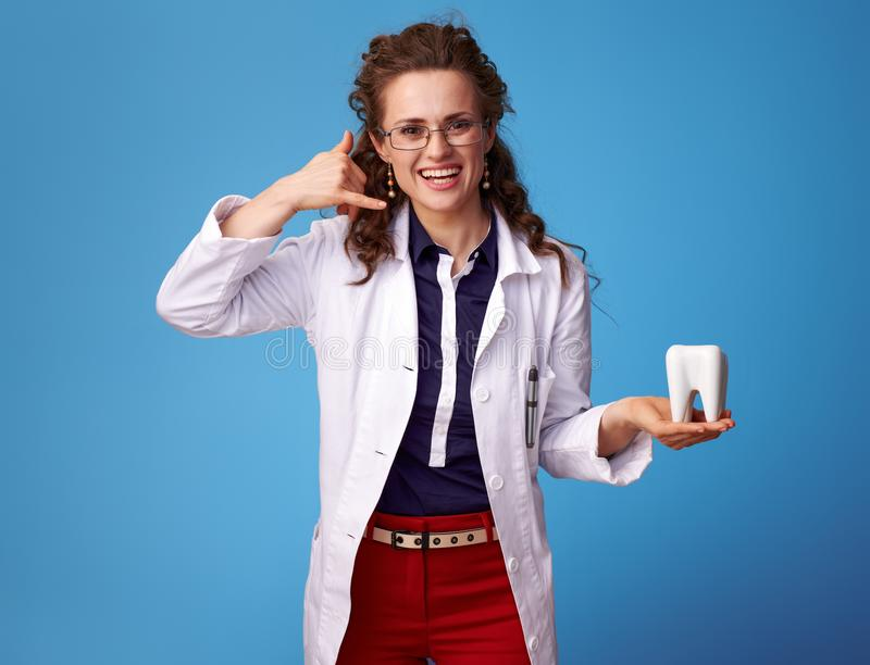 Physician woman showing call me gesture and tooth on blue. Happy physician woman in white medical robe showing call me gesture and a tooth against blue royalty free stock photos