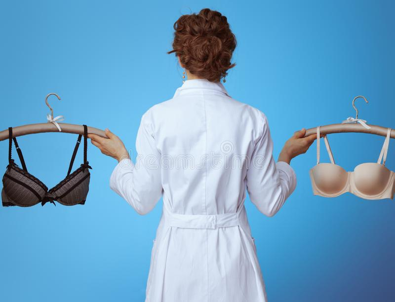 Physician woman showing comfortable bra and sexy bra on blue stock photo