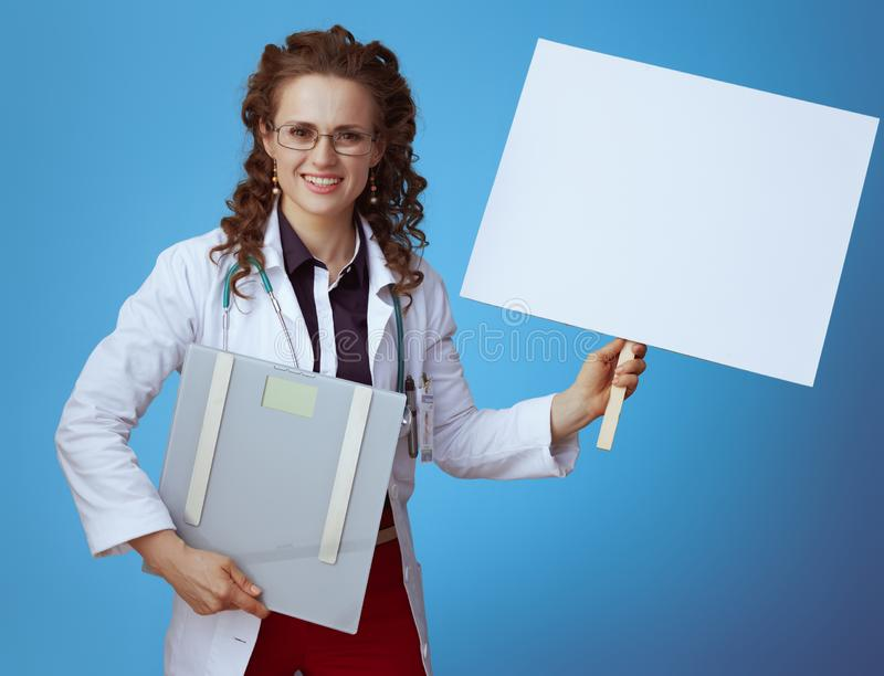 Physician woman with weight scale showing blank placard on blue. Smiling elegant physician woman in bue shirt, red pants and white medical robe with weight scale stock photos