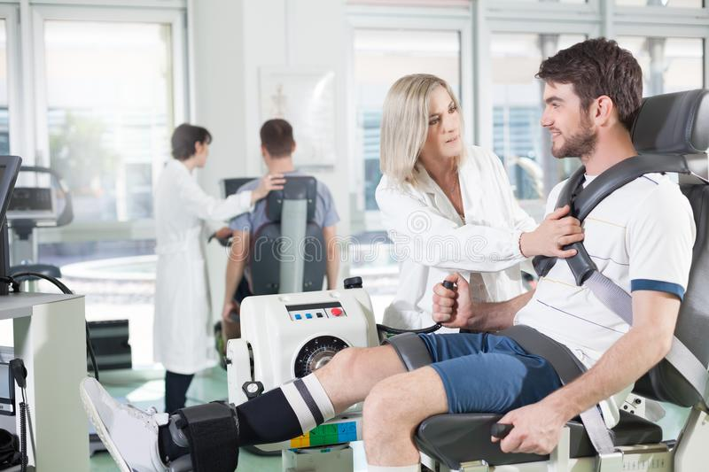 Gym physiatric rehabilitation. Physicians with patients in a gym for physical rehabilitation dynamometer in the foreground and in the background cycle ergometer royalty free stock images