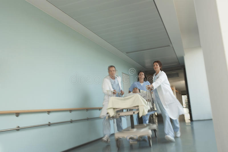 Physicians Rushing Patient On Gurney Down Hospital Corridor royalty free stock photography