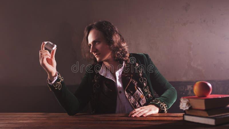 Physik die Wissenschaft der Natur, das Konzept des Studierens der Naturgesetze Ein junger Mann im Bild von Isaac Newton stockfoto