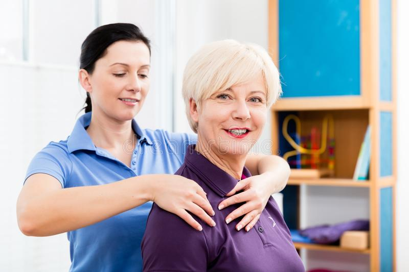 Masseuse applying neck massage on older woman. Physio giving shoulder massage to patient stock photo