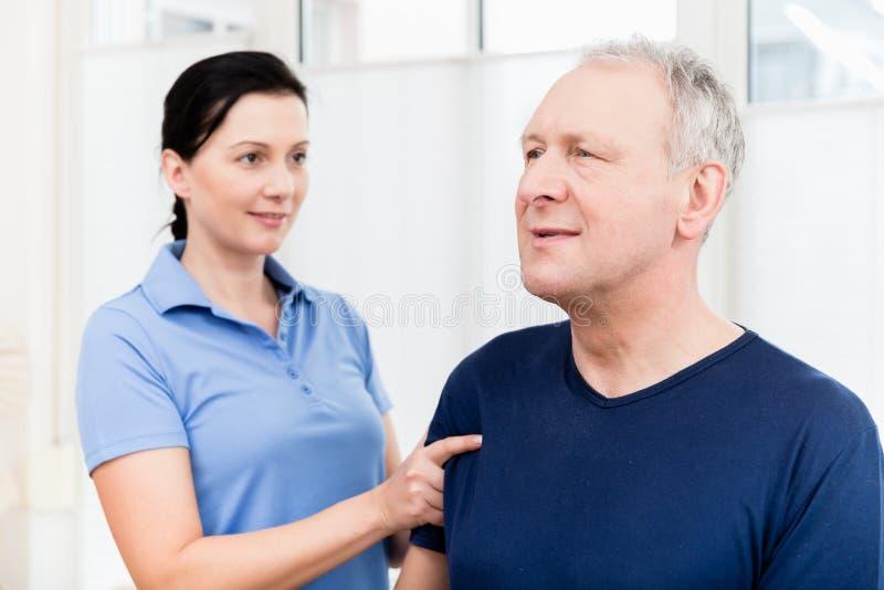 Physio giving shoulder massage to patient. Masseuse applying neck massage on older man stock photo