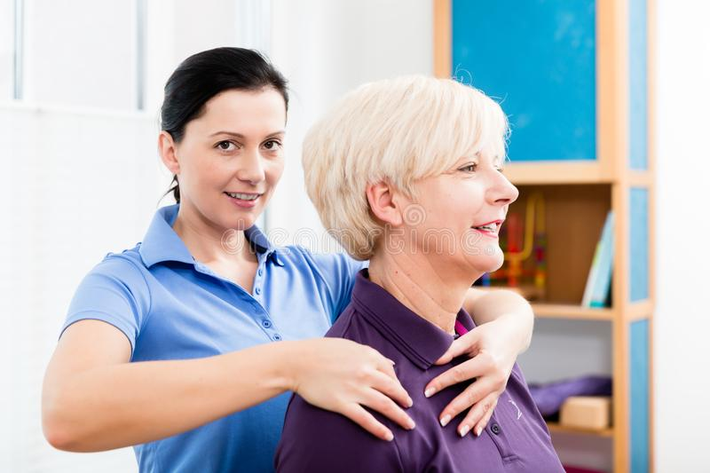 Masseuse applying neck massage on older woman. Physio giving shoulder massage to patient stock photography