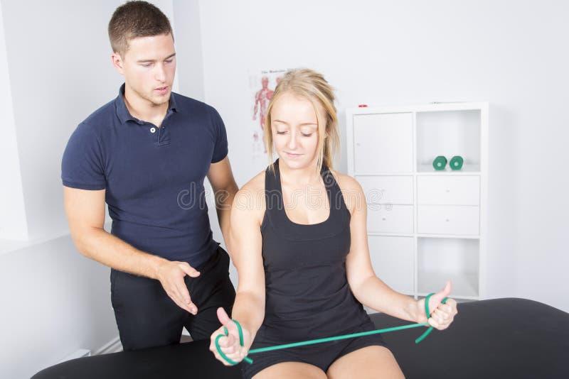 Physio- patient de aide masculin de thérapeute et de femme image libre de droits