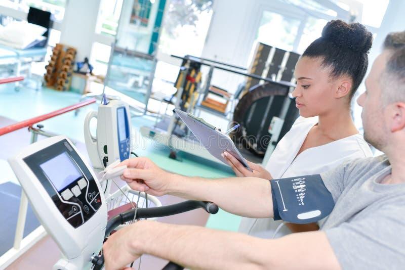 Physio- thérapeute féminin travaillant avec le patient masculin image stock