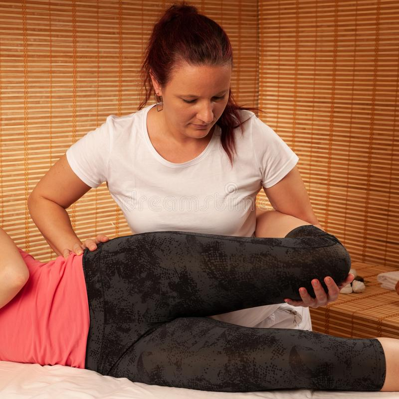 Physio- thérapie - thérapeute travaillant aux jambes patientes pour augmenter m photos stock