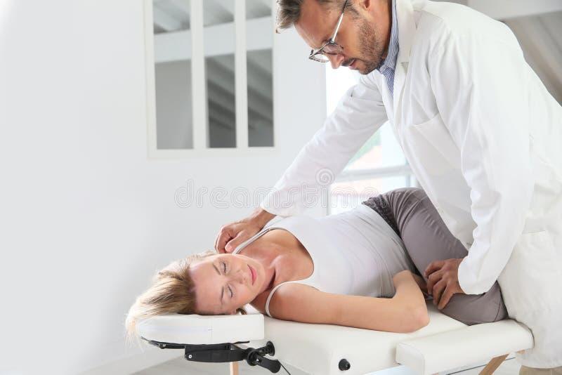 Physiothérapeute étirant le corps de la femme photo stock