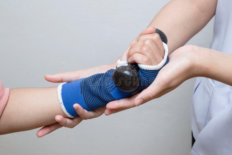 Physiothérapeute aidant la femme patiente dans les haltères de levage images stock