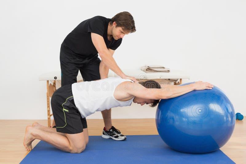 Physiothérapeute aidant le jeune homme avec la boule de yoga image libre de droits