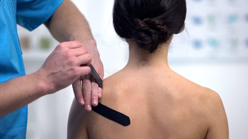 Physiothérapeute appliquant les bandes en 'y' sur la tension patiente femelle de muscle d'épaule image stock
