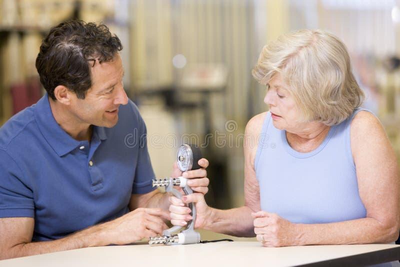 Physiothérapeute avec le patient dans la réadaptation photo stock