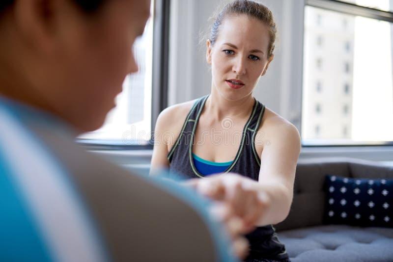 Physiothérapeute caucasien de femme parlant à un patient féminin chinois de mi-adulte et prenant des notes sur un comprimé pendan image stock