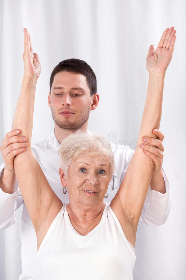 Physiothérapeute et femme agée pendant la réadaptation image stock