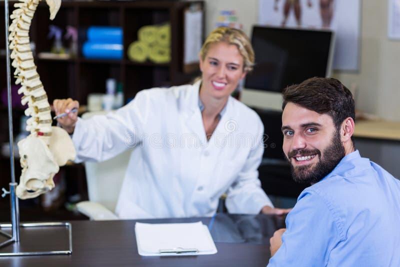 Physiothérapeute expliquant le modèle d'épine au patient photographie stock