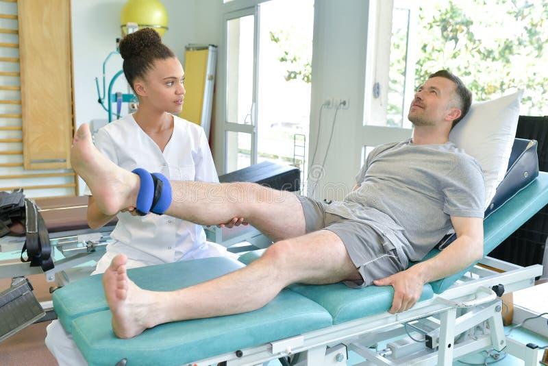 Physiothérapeute féminin massant le patient de jambe photographie stock