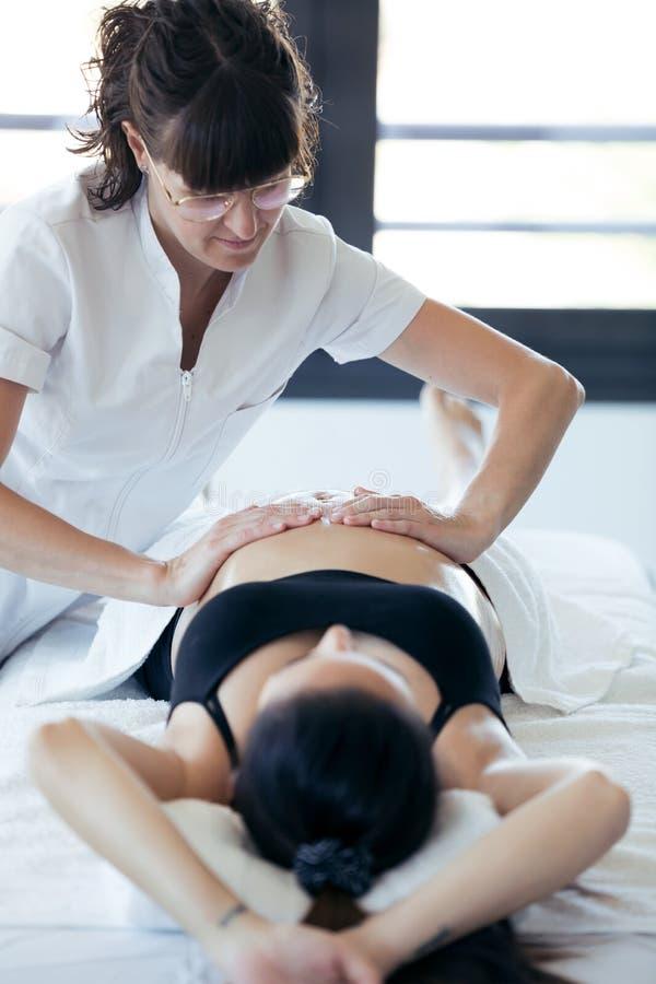Physiothérapeute féminin massant le ventre sur la femme enceinte au centre de station thermale photos stock