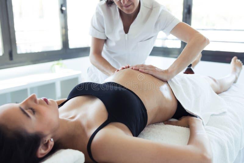 Physiothérapeute féminin massant le ventre sur la femme enceinte au centre de station thermale image libre de droits