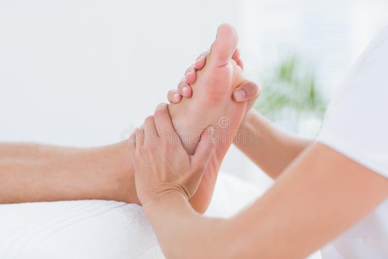 Physiothérapeute faisant le massage de pied photo libre de droits