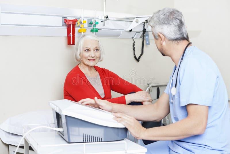 Physiothérapeute masculin de regard patient supérieur Using Machine photographie stock libre de droits