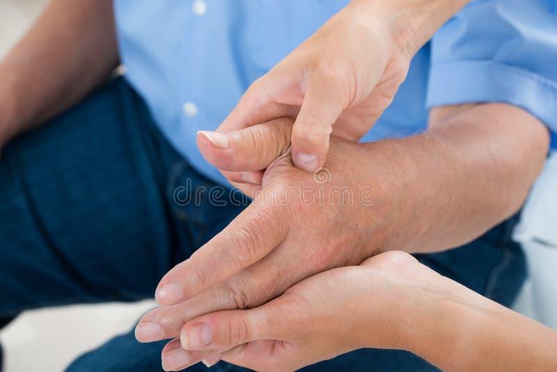 Physiothérapeute Massaging Palm Of un homme photographie stock