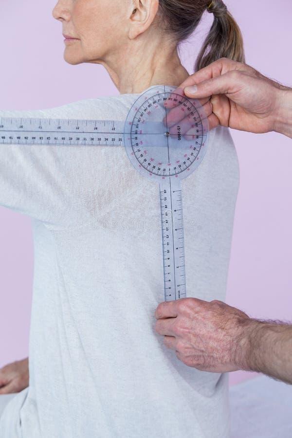 Physiothérapeute mesurant les patients féminins de retour avec la règle médicale photos libres de droits
