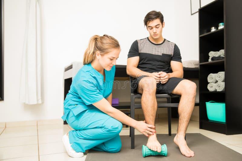 Physiothérapeute Treating Plantar Fasciitis dans l'athlète photo stock