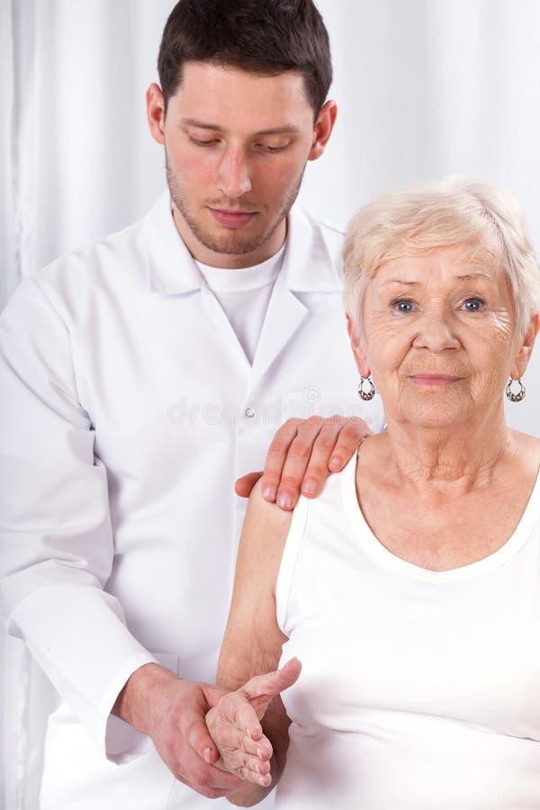 Physiothérapeute vérifiant des capacités de moteur de bras photos libres de droits