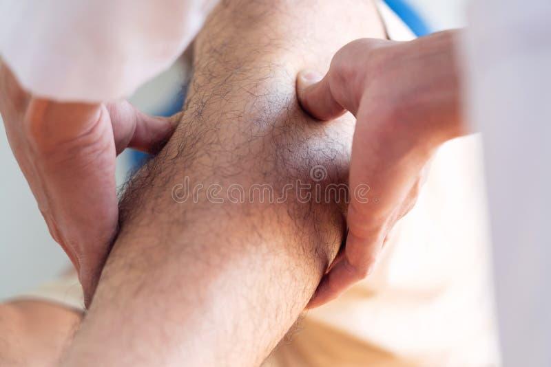 Physioth?rapie de consultation de r?adaptation de docteur de physioth?rapeute donnant exer?ant le traitement de jambe avec le pat photographie stock libre de droits