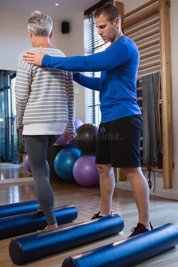 Physiotherapeut, der ältere Frau unterstützt, wenn Übung auf Schaumrolle durchgeführt wird lizenzfreies stockfoto