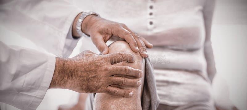 Physiotherapeut, der der älteren Frau Knietherapie gibt lizenzfreie stockfotografie