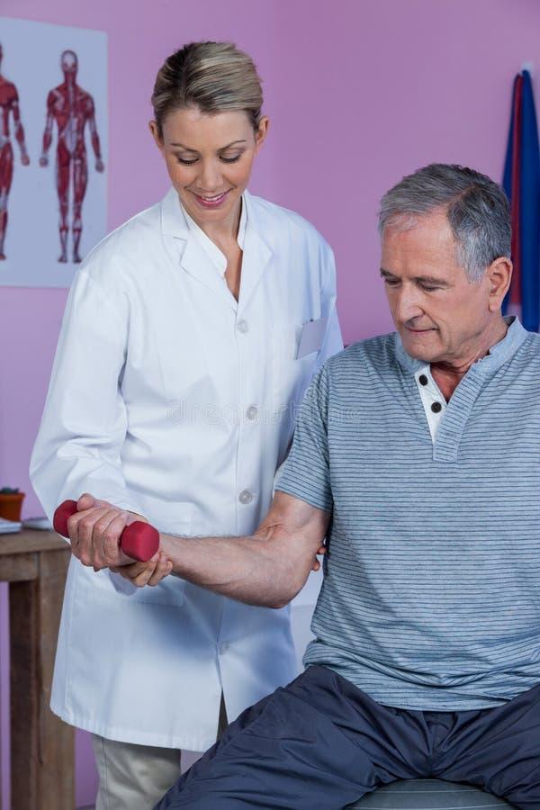Physiotherapeut, der älteren Mann unterstützt, um dumbbellanzuheben stockfotografie