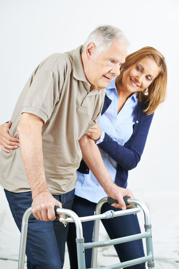 Physiotherapeut, der altem älterem Mann hilft stockbild