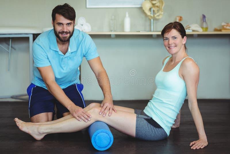Physiotherapeut, der Beintherapie eine Frau verwendet Schaumrolle antut stockbild