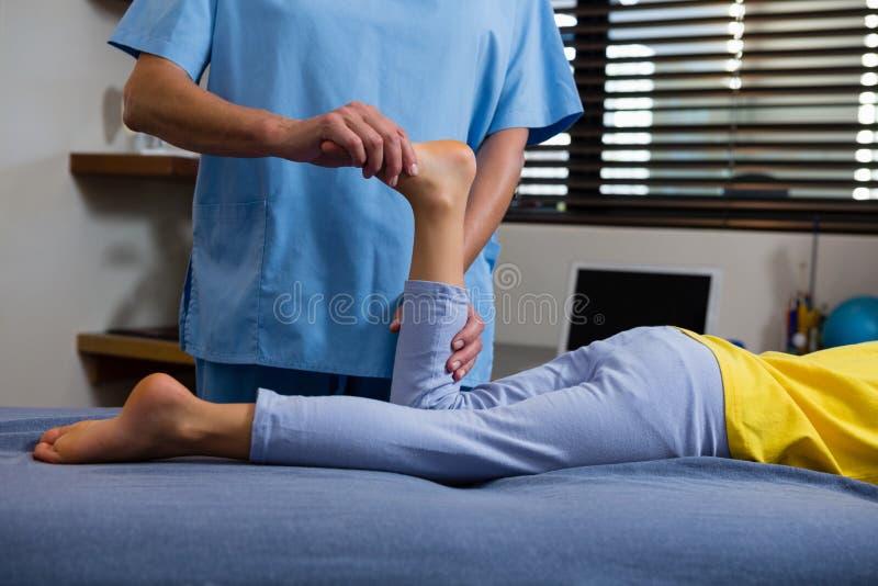 Physiotherapeut, der dem Mädchen Physiotherapie gibt stockfotos